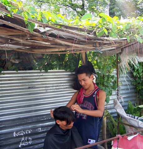 Filipino entrepreneurship: If you've the determination and skill, it doesn't take much for a Filipino to set up a business. This barber charges Php20 for a haircut in his roadside 'salon' in the Reclamation Area in Bacolod City and is doing good business. (Photo: Robert Harland)