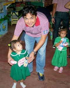 Incoming Marapara Rotary president  Rico Cajili serves lunch to a child at the  Villa Gracia Day Care Center