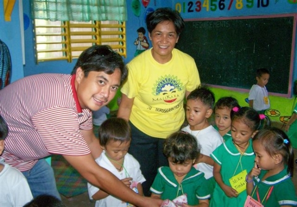 A surprise party for the children of the Villa Gracia Day Care Center. Incoming Marapara Rotary president Rico Cajili and teacher Mary Ann Fernandez serve the children with lunch