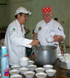Marapara Rotary president Chef Rico Cajili (left) and club director and NDB contributor Chef Robert Harland serve up bowls of Arroz Caldo