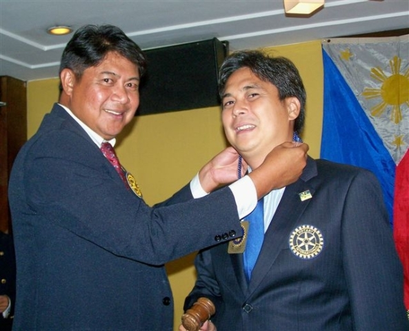 Outgoing Bacolod Marapara Rotary Club president Maximo Javelona (left) hands over the club gavel and Rotary medallion to incoming president Jose Rico Cajili