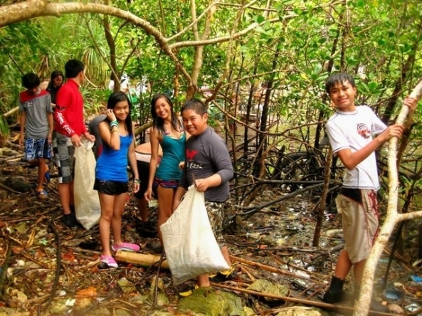 Youngsters taking part in a coastal clean-up as part of a youth  marine and wildlife camp on Danjugan Island