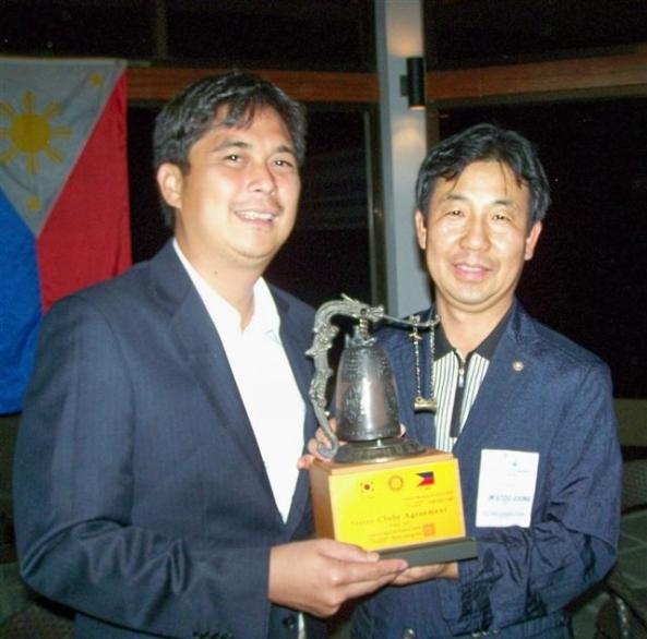 Ilsan-Jungbal Rotary president Kim Gyoo Joong (right) presents Marapara Rotary president Rico Cajili with a decorative Korean Rotary bell