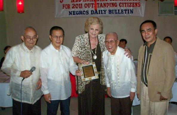 Hazel Andrea-Stuart receives her award from (l-r) Henry Streegan, the Negros Daily Bulletin's editorial consultant; Pert Toga, president and editor-in-chief; Rolly Espina, chairman and John Elmer Ubaldo, president of the Negros Press Club.