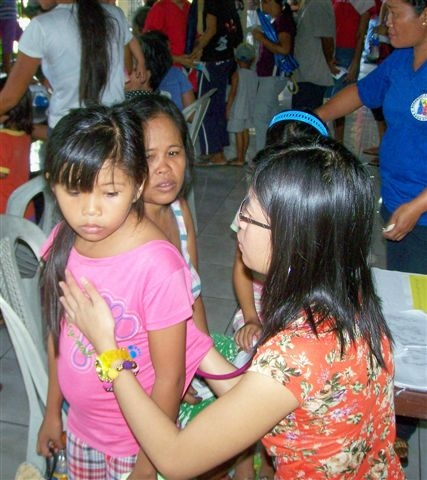 A volunteer doctor examines a young patient
