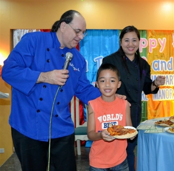 Eight year-old Jadon Kilayko was awarded the most interesting pizza by Italian chef Carmine Pece. Looking on is Pearl Manor Skills Academy director chef Shangrila Chua