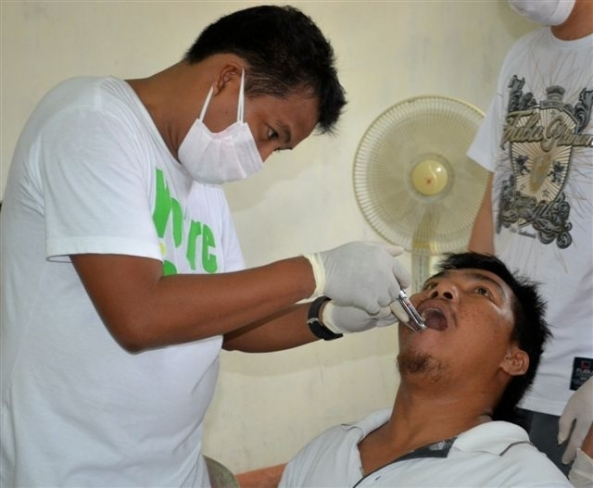 Marapara Rotary member and dentist, Dr. Selwyn Lloyd Baloyo looking after a patient