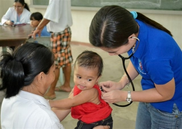 A volunteer doctor examines this baby boy from Bata