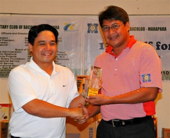 Patrick Lacson (left) receives the champion's trophy from Marapara Rotary past president Max Javelona