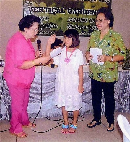 Garden Cub president Peps Remitio inducts seven year-old Lorien Ysobel Gamboa. Looking on is club membership committee chair Daphne Javelosa