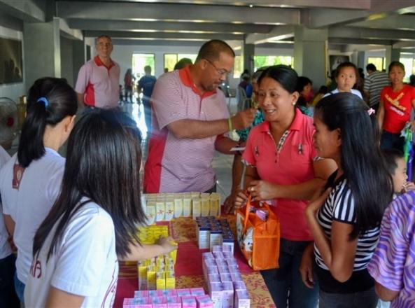 Club director Fidel Henares handing out free medicines to barangay members