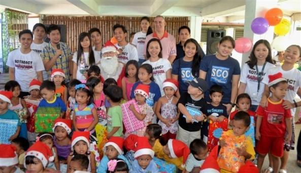 Santa with children from the Villa Gracia Day Care Center, Rotarians, Rotoractors and St. Scholastica Student Council representatives