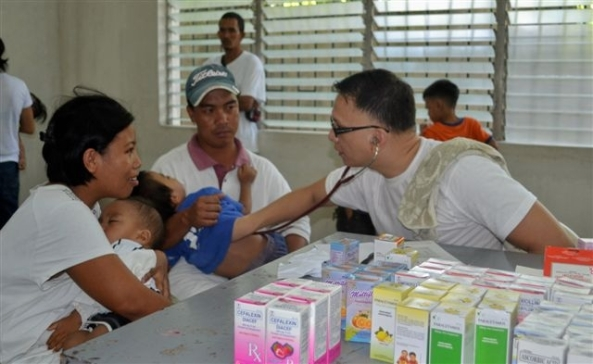 """Bacolod lone district Congressman Tony """"Doc"""" Golez examines a young boy from Brgy. Bata"""
