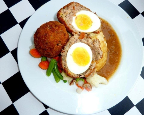 Scotch egg halved and served with mashed potato, gravy and vegetables